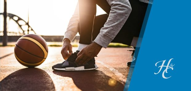 Man tying his shoe with basketball nearby on outdoor court