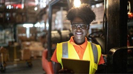 Warehouse worker in safety vest with tablet